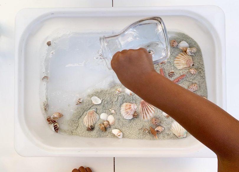 activité enfants : verser l'eau dans le bac sensoriel sur l'océan