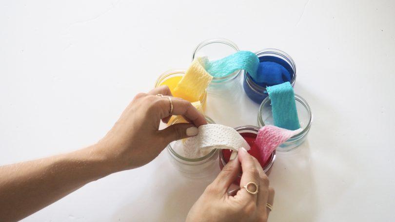 Placer l'essuie-tout dans chaque récipient pour qu'il s'imbibe de couleur.