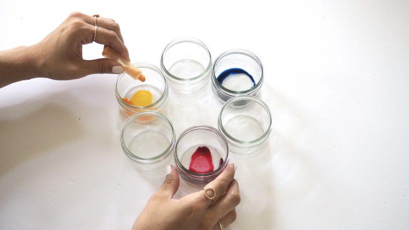 Déposer quelques gouttes de colorant alimentaire au fond des récipients.
